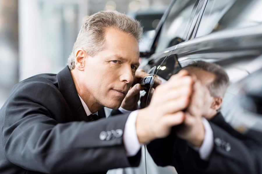mann besiktiger bil